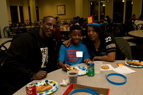 Student from St. Paul's School with his parents playing Headbanz game